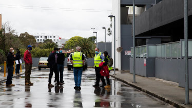 Home inspectors gather outside the Charles Street development on Wednesday afternoon.