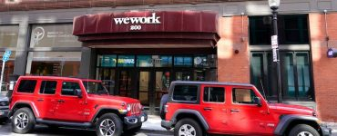 The WeWork logo sits on the facade of a commercial real estate office in Boston.